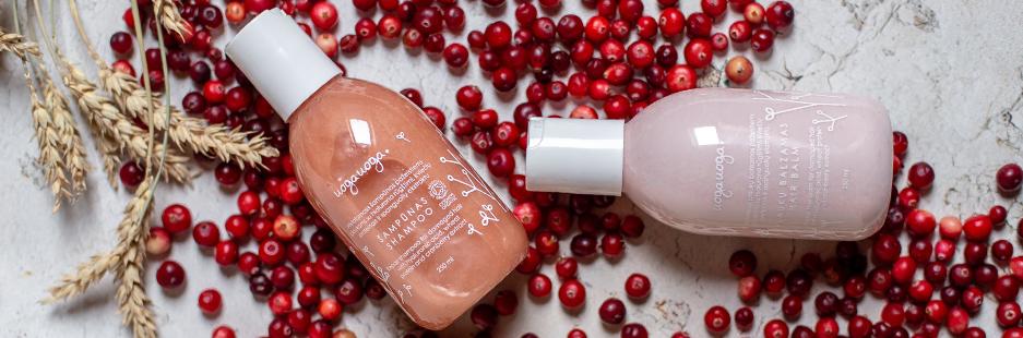 Šampūno ir kondicionieriaus buteliukai spalnguolių fone